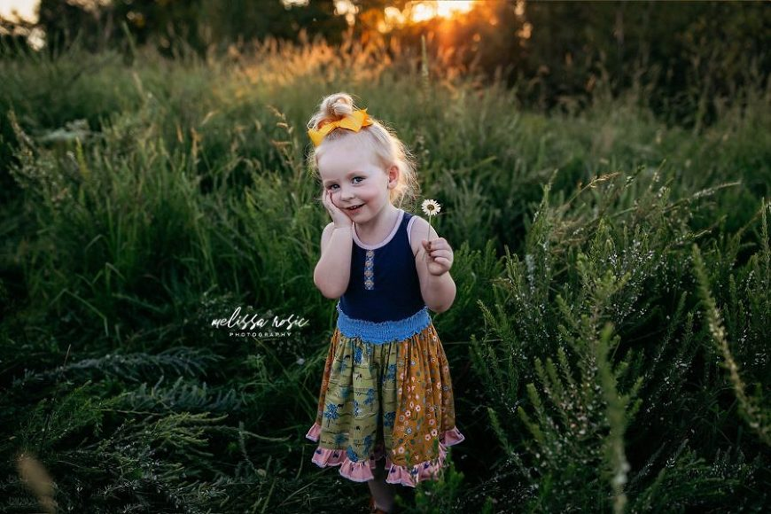 Little girl holding wildflower and smiling with hand on cheek, Melissa Rosic Photography Daily Fan Favorite