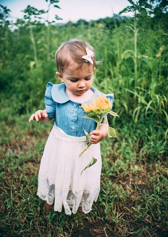 Toddler girl in lacy skirt holding sunflower, Beyond the Wanderlust Daily Fan Favorite