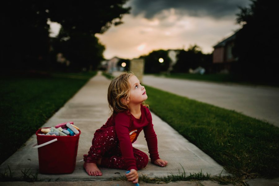 Girl coloring on sidewalk looking up at sky, Beyond the Wanderlust Daily Fan Favorite