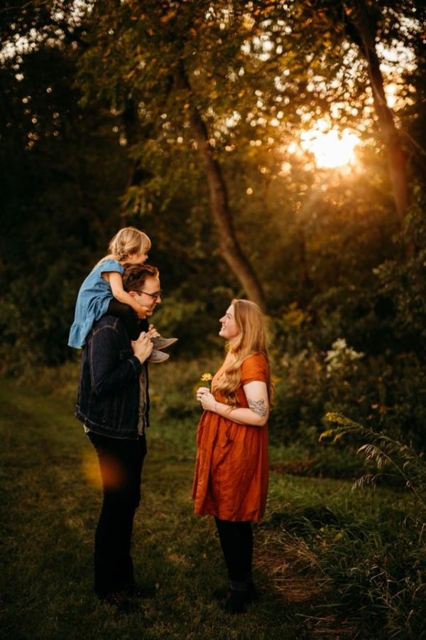 Man and woman smiling at each other with toddler on his shoulders, Made Beloved Photography Daily Fan Favorite