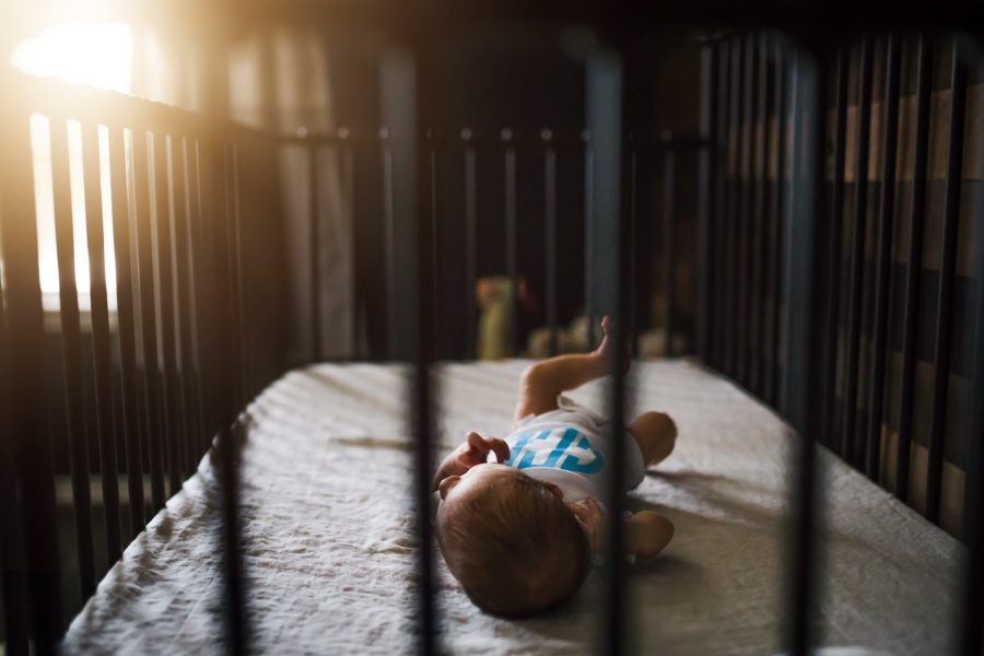 Newborn lying in crib looking at sun out window, Angela Kim Photography Daily Fan Favorite