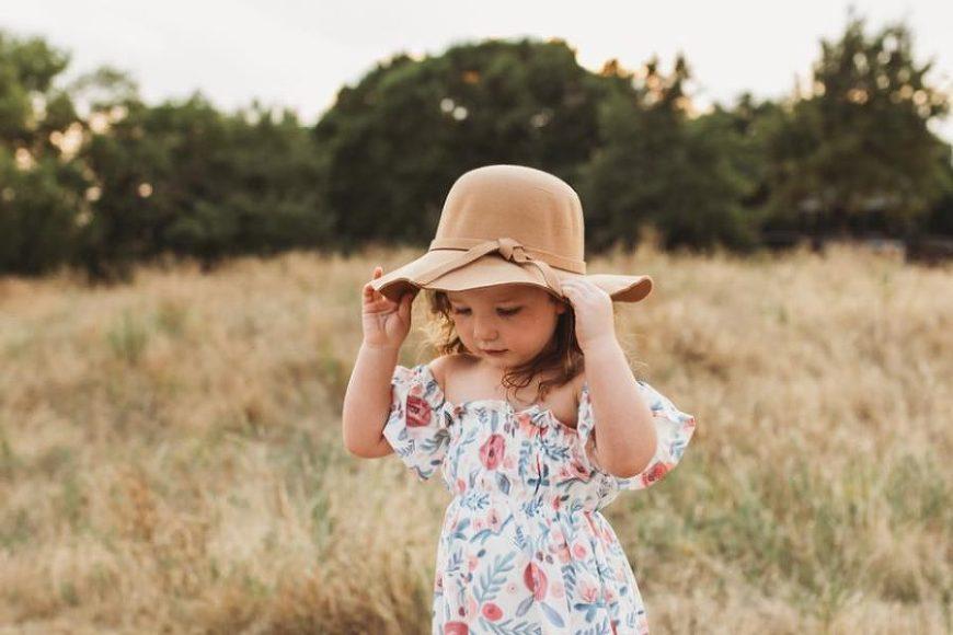 Little girl standing in field touching hat wearing floral dress, Beyond the Wanderlust Daily Fan Favorite
