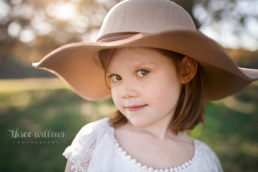 Portrait of girl looking at camera with sly grin under brim of hat, Beyond the Wanderlust Daily Fan Favorites