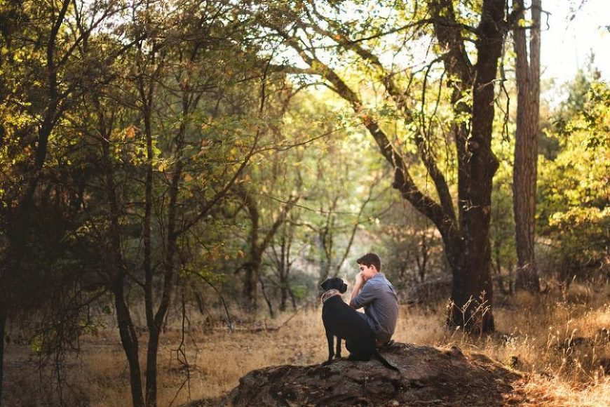 Boy sitting in woods with dog looking at each other, Beyond the Wanderlust Daily Fan Favorites