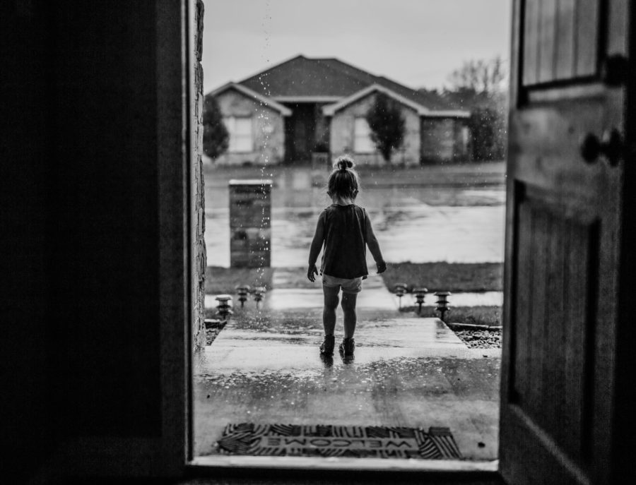 Child standing in rain outside front door, Brittany Skeele photography Daily Fan Favorite