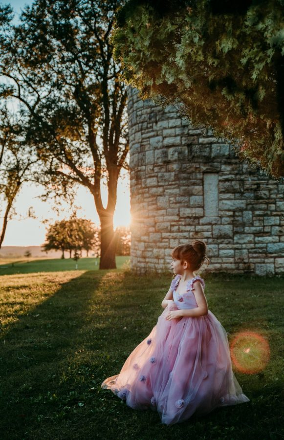 Girl in purple dress standing in grass with sun flare in background, Beyond the Wanderlust Daily Fan Favorites