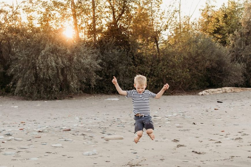 Boy jumping in sand with golden light behind him in trees, Beyond the Wanderlust Daily Fan Favorites