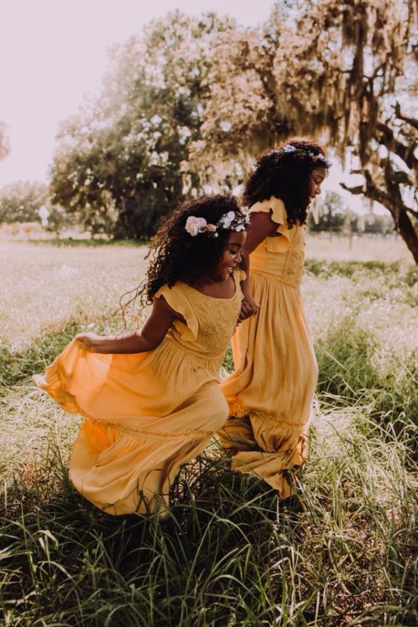 Girls in yellow dresses holding hands walking through outdoor field, Beyond the Wanderlust Daily Fan Favorite