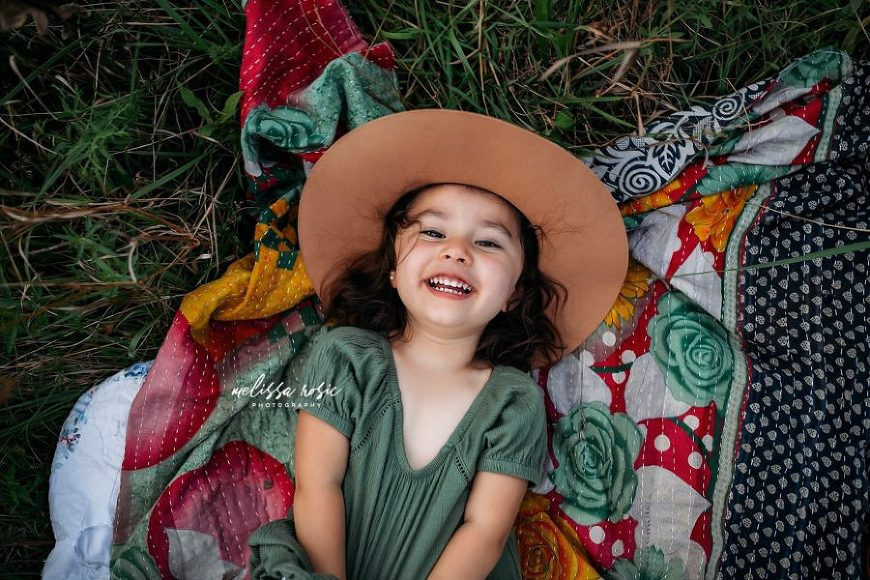 Girl smiling lying on quilt with hat, Melissa Rosic Photography Daily Fan Favorite