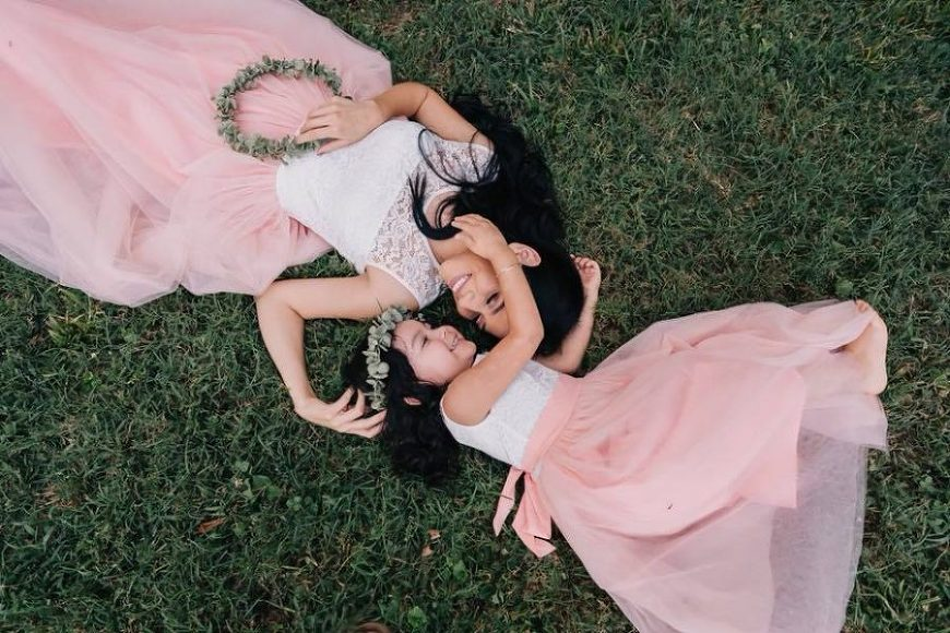 Overhead picture of mother and daughter in matching dresses lying on grass, Beyond the Wanderlust Daily Fan Favorite