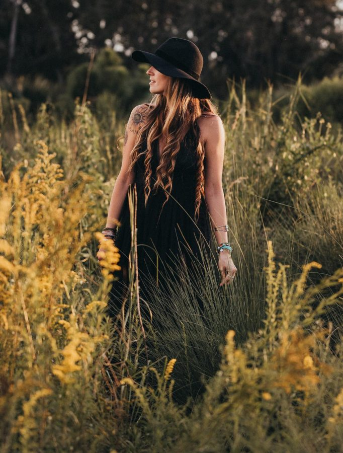 Woman with long hair standing in long grasses with black dress and hat, Beyond the Wanderlust Daily Fan Favorites