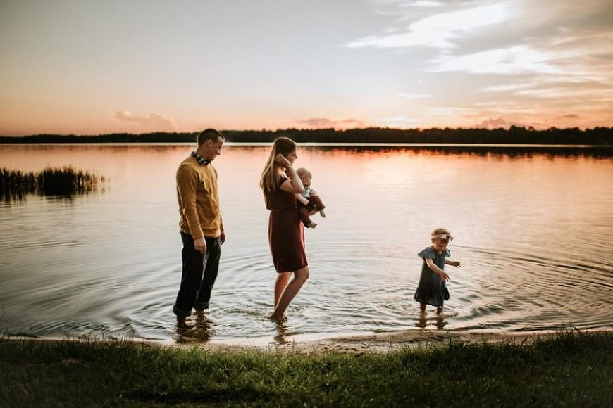 Family walking at edge of lake in water during sunset, Rebecca Fleming Photography Daily Fan Favorite