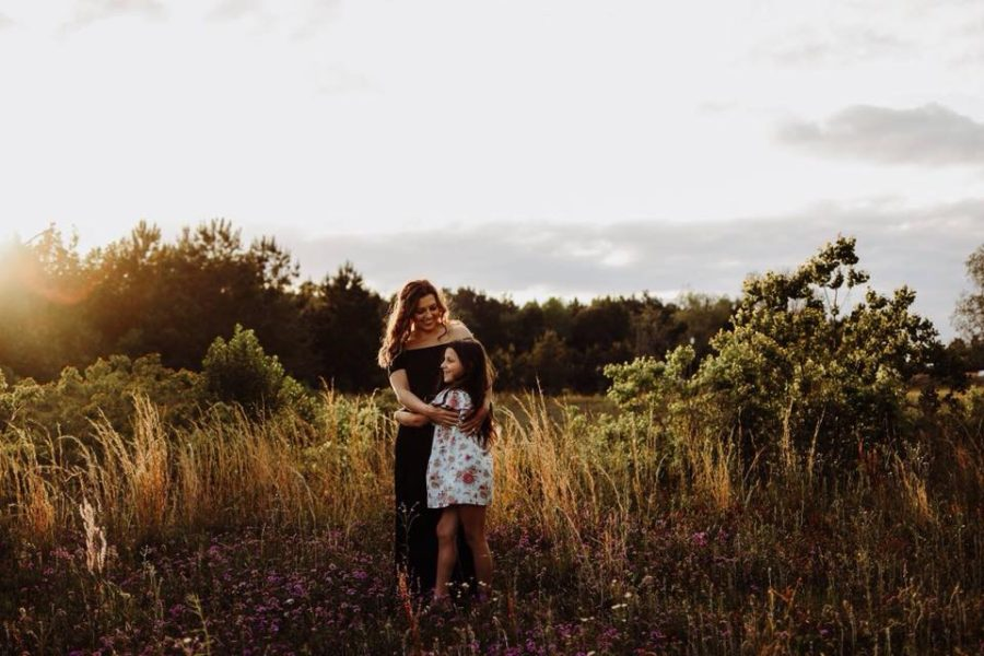 Woman and girl embracing in field, Beyond the Wanderlust Daily Fan Favorites