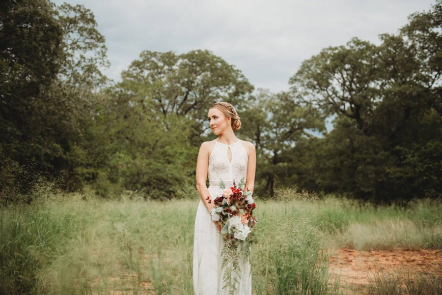 Portrait of woman in wedding gown holding boquet with woods behind her, Beyond the Wanderlust Daily Fan Favorite