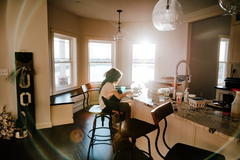 indoor natural light, light flare, young girl eating breakfast in morning light, lifestyle inhome pictures