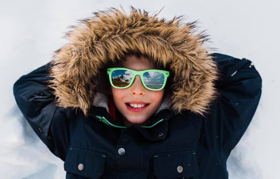 spring in Minnesota, upclose kid pictures, boy with sunglasses on, boy laying in snow