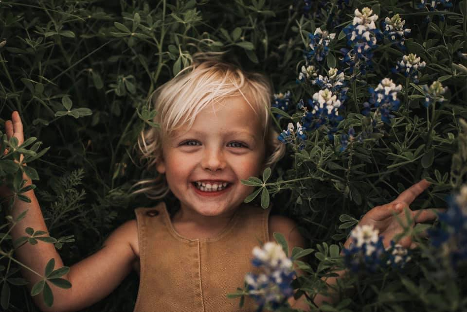 spring pictures of kids, happy girl laying down in flowers, spring flowers