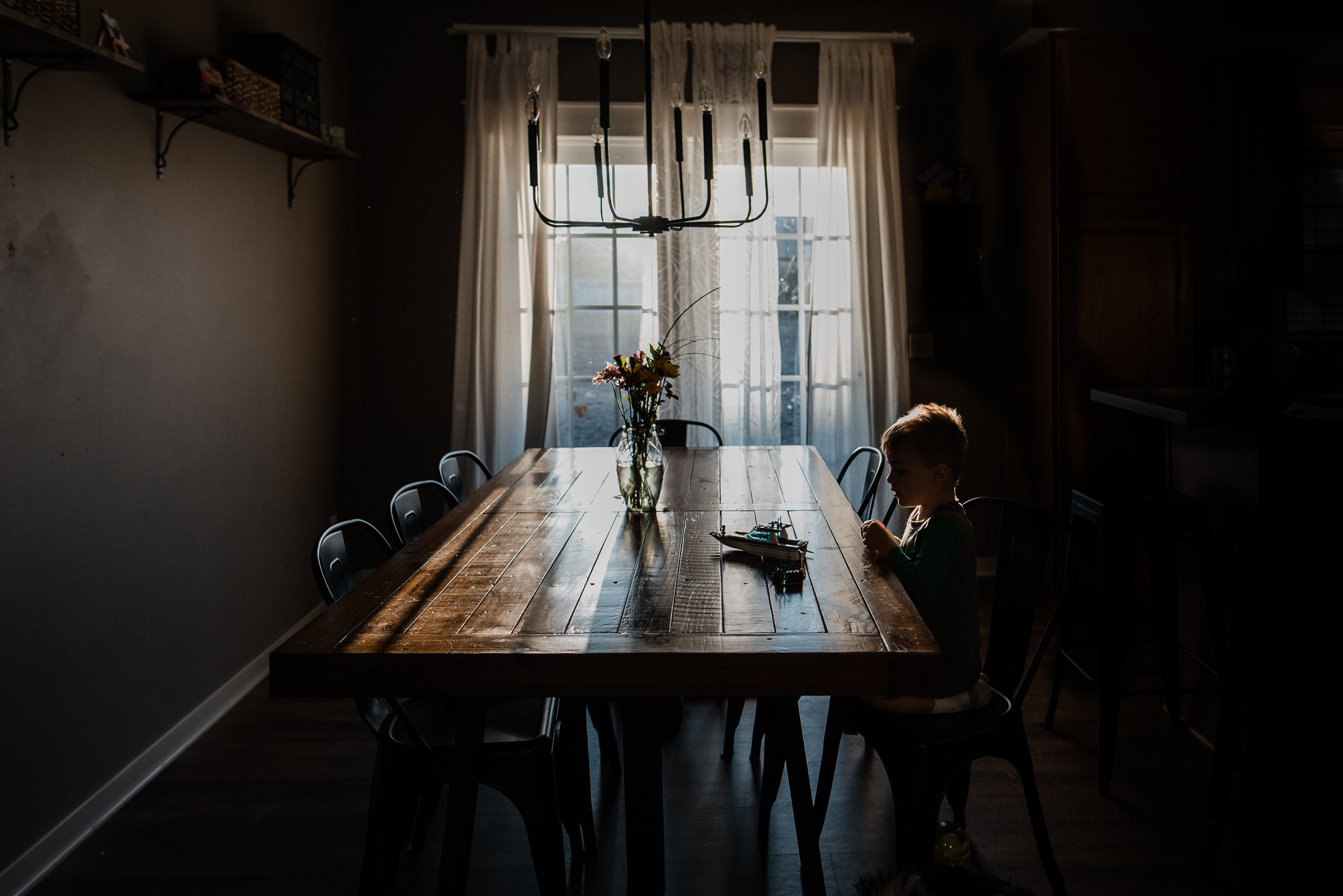 indoor natural light pictures, lifestyle kid pictures, boy sitting at table with natural light