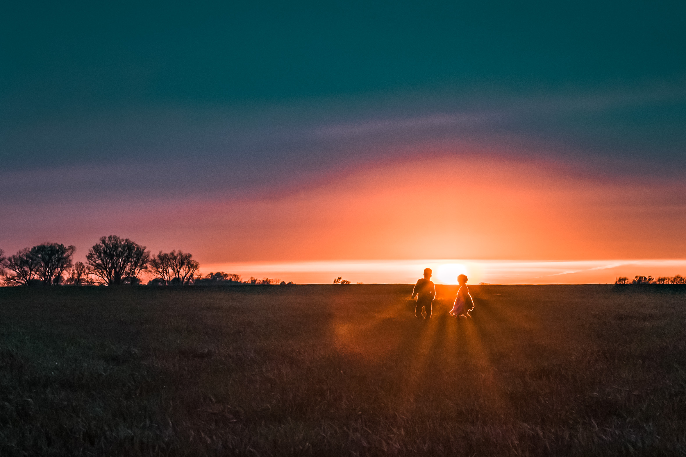 beautifully colored sunset - siblings playing at dusk - country