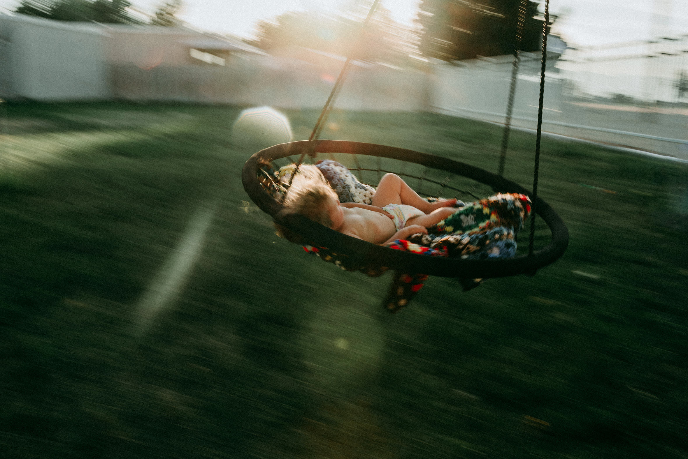 panning image, child riding hammock, blurred, motion, lifestyle kid picture, summertime