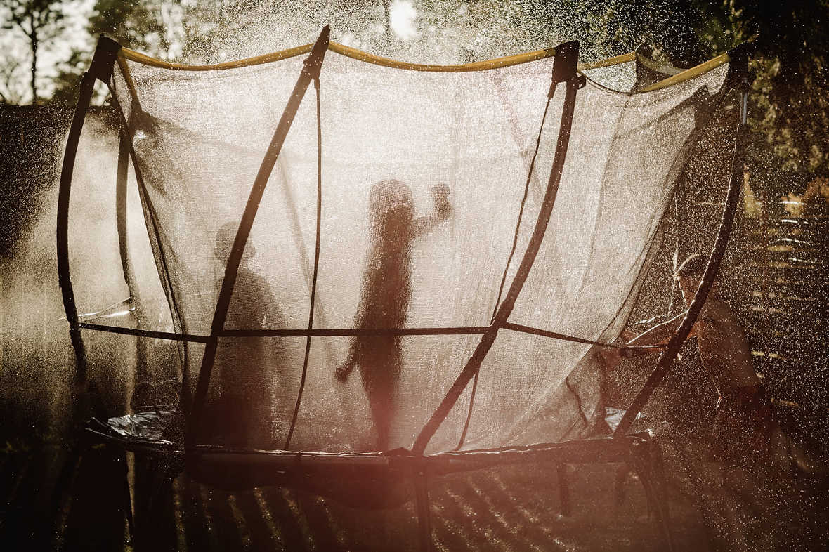 kids on trampoline, summertime, mist, light and shadow, documentary lifestyle lifestyle pictures