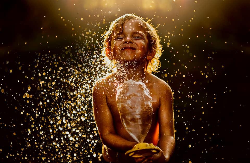 summertime, sprinkler, water from hose, little boy playing in water, backlighting